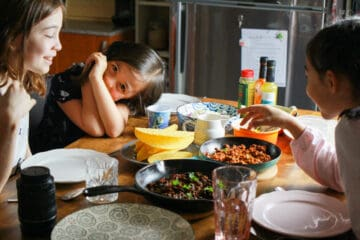 Photo of my family around the kitchen table getting ready to eat a meal of black bean tacos.